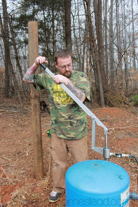 Jerry using hand pump on well