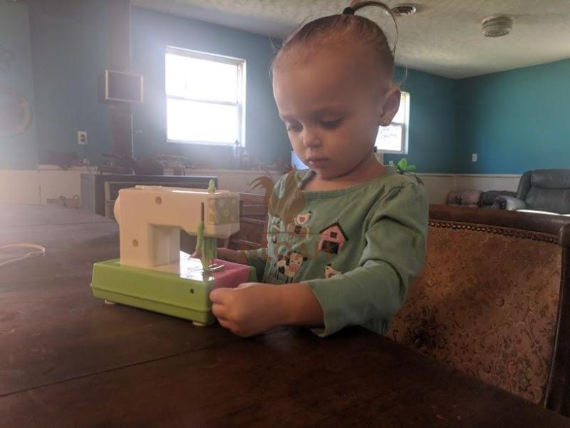 child playing with vintage sewing machine