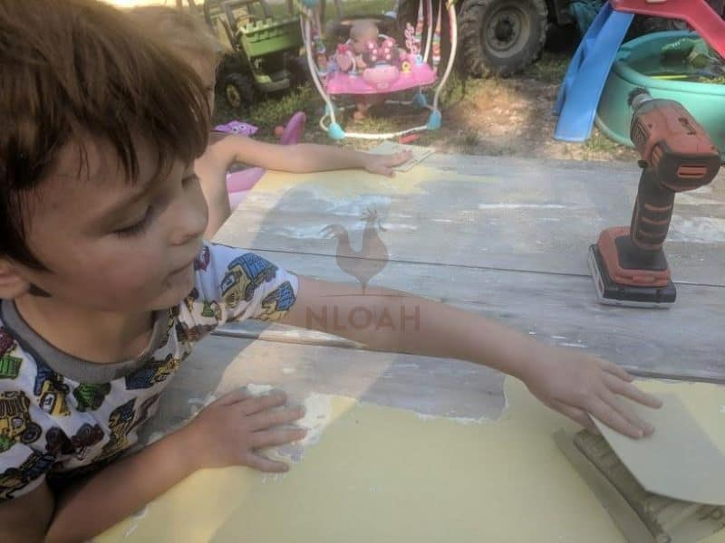 boy using sanding block to remove old paint from table