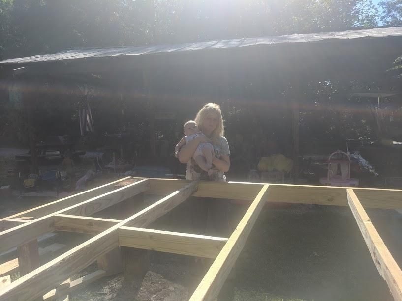 brea and her daughter looking over the diy playhouse