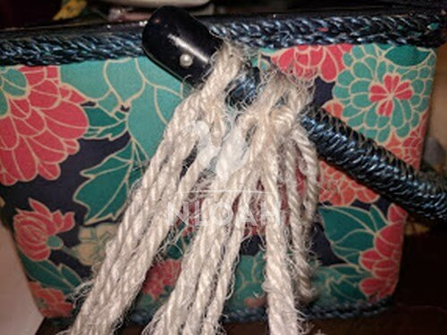 curly yarn tied tohandle of sewing basket