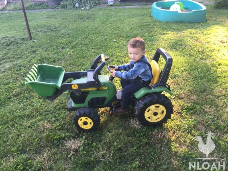 boy driving a motorized toy excavator