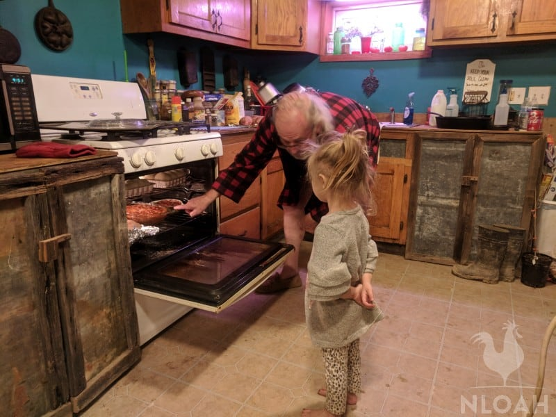 little girl looking at food in oven