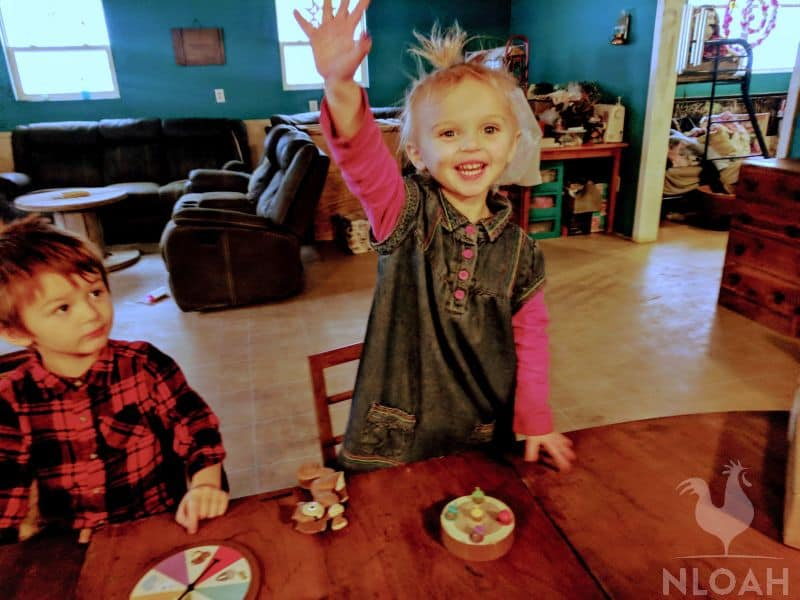 little girl raising hands in homeschool classroom