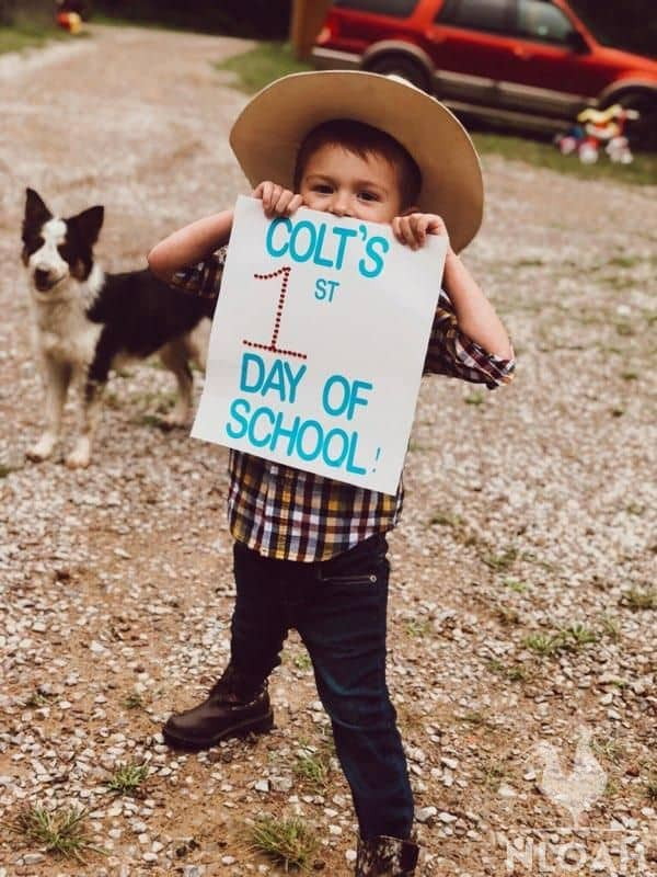 little boy holding a sign on his first school day
