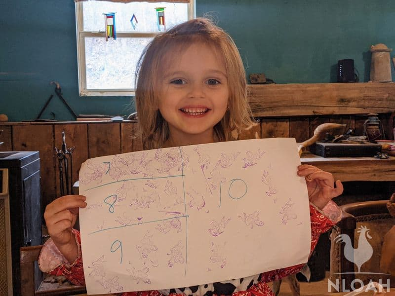 little girl showing her solved math problem